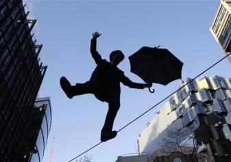 A man dressed as a city gentleman walks across a tightrope in London's financial district